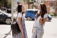 两个年轻的俏丽的亭亭玉立的女孩、佩带的偶然成套装备、立场在街道和闲谈 库存照片