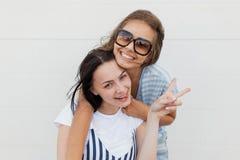 两个年轻的深色头发的女孩,佩带的偶然成套装备,可爱的拥抱和看照相机 库存照片