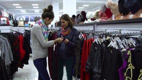 两个年轻美丽的女孩选择在一个时兴的精品店的衣裳 女孩小心地看衣裳并且审查它 股票录像