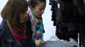 两个年轻美丽的女孩选择在一个时兴的精品店的衣裳 女孩小心地看衣裳并且审查它 股票视频