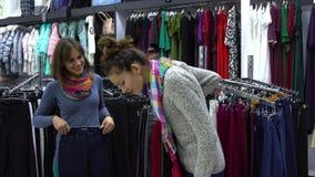 两个年轻美丽的女孩选择在一个时兴的精品店的衣裳 女孩小心地看衣裳并且审查它 影视素材