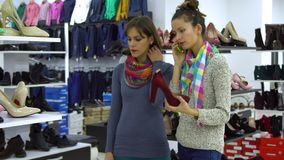 两个年轻美丽的女孩选择在时尚精品店的鞋子 女孩看殷勤地鞋子并且审查它 影视素材