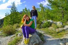 两个年轻美丽的白肤金发的女孩和红头发人在一个岩石在sunn 库存图片