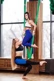两个年轻运动女孩浅黑肤色的男人和金发碧眼的女人做着在绿色空中丝绸的健身在现代健身房 免版税库存照片