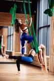 两个年轻运动女孩浅黑肤色的男人和金发碧眼的女人做着在绿色空中丝绸的健身在现代健身房 库存图片