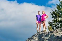 两个年轻运动的女孩站立在山顶部的-胜利 免版税图库摄影