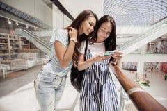 两个年轻逗人喜爱的稀薄的深色头发的女孩,立场紧挨着在一个现代购物中心 库存图片