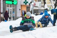 两个幼儿从雪幻灯片搬出 免版税图库摄影