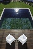 两个庭院椅子和游泳池视图和木甲板 免版税图库摄影
