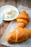 两个开胃新月形面包用在一张木桌上的黄油 库存照片