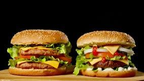 两个开胃汉堡特写镜头用转动在黑背景的芝麻小圆面包,快餐无缝的使成环的射击 股票视频
