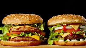 两个开胃汉堡特写镜头用转动在黑背景的芝麻小圆面包,快餐无缝的使成环的射击 股票录像
