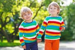 两个弟弟孩子在五颜六色的衣物走的手上我 库存图片