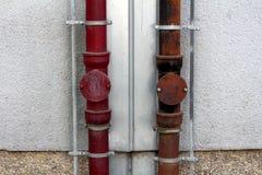 两个强的生锈的金属天沟降雨量管子被连接到在地方公寓的边登上的双方的避雷针 库存图片