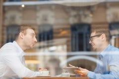 两个微笑的人讨论工作问题在咖啡馆 库存图片