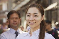 两个微笑的商人,在女实业家的焦点画象,户外,北京 免版税库存图片