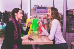 两个微笑的女孩吃蛋糕和谈话在咖啡馆 免版税图库摄影
