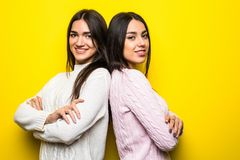 两个微笑的女孩画象在紧接站立和看照相机的毛线衣穿戴了被隔绝在黄色背景 库存照片