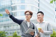两个微笑的男性工作工友户外一起谈话在a 库存图片