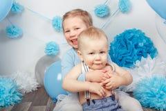 两个微笑的笑的拥抱的逗人喜爱的可爱的白种人孩子、小孩女孩和男婴,庆祝生日 免版税库存照片