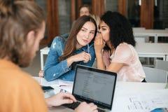 两个微笑的美丽的女孩坐在教室和说闲话,当工作年轻的人在他的膝上型计算机时 俏丽的女孩与 库存图片