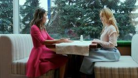 两个微笑的美丽的少妇谈话在咖啡馆的桌上 库存照片
