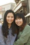 两个微笑的年轻朋友画象靠近在北京户外 免版税图库摄影
