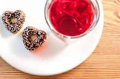 两个心形的巧克力曲奇饼用五颜六色的糖果在上面、玻璃与酸樱桃汁和一块白色板材洒 免版税库存照片