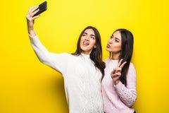 两个快乐的女孩画象在站立和采取selfie的毛线衣穿戴了被隔绝在黄色背景 库存照片
