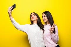 两个快乐的女孩画象在站立和采取selfie的毛线衣穿戴了被隔绝在黄色背景 免版税库存照片