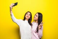 两个快乐的女孩画象在站立和采取selfie的毛线衣穿戴了被隔绝在黄色背景 免版税库存图片