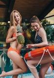 两个快乐的女性朋友获得乐趣在与菠萝和救生圈圆环的游泳池跳舞 免版税图库摄影