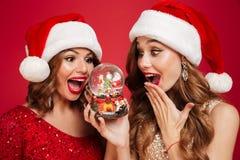两个快乐的少妇画象圣诞节帽子的 图库摄影