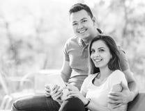 两个快乐的恋人坐长沙发 免版税库存照片