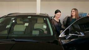 两个快乐的梦想的女孩在陈列室里选择一辆新的汽车 股票视频
