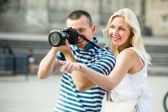 两个快乐的游人在手上的拿着照相机 免版税库存照片