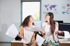 两个快乐的美丽的年轻企业女孩在办公室 免版税库存图片