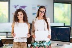 两个快乐的美丽的年轻企业女孩在办公室 库存照片