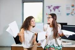 两个快乐的美丽的年轻企业女孩在办公室 库存图片