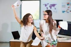 两个快乐的美丽的年轻企业女孩在办公室 免版税图库摄影