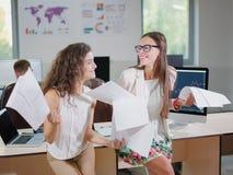 两个快乐的美丽的年轻企业女孩在办公室 图库摄影