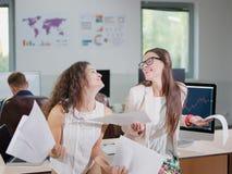 两个快乐的美丽的年轻企业女孩在办公室 免版税库存照片