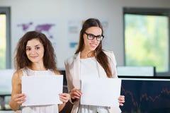 两个快乐的美丽的年轻企业女孩在有白色纸片的办公室 免版税库存图片