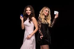 两个性感的女孩浅黑肤色的男人和金发碧眼的女人,摆在与芯片和卡片在他们的手上,啤牌概念黑色背景 免版税库存图片
