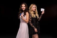两个性感的女孩浅黑肤色的男人和金发碧眼的女人,摆在与芯片和卡片在他们的手上,啤牌概念黑色背景 免版税图库摄影
