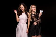 两个性感的女孩浅黑肤色的男人和金发碧眼的女人,摆在与芯片在她的手上,啤牌概念黑色背景 免版税库存图片