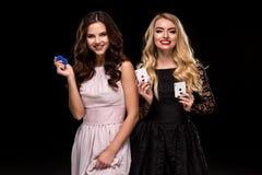 两个性感的女孩浅黑肤色的男人和金发碧眼的女人,摆在与芯片在她的手上,啤牌概念黑色背景 库存图片