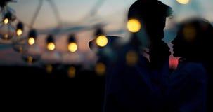 两个恋人剪影的浪漫画象  人亲吻他的恋人的手,当站立在后时 股票录像