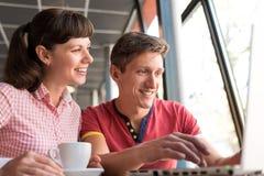 两个恋人聊天和获得乐趣在咖啡馆 免版税图库摄影