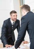 两个恼怒的商人画象在衣服的 免版税库存照片